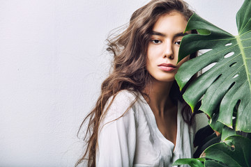 Young beautiful girl model Asian brunette with long hair posing in Studio with tropical plant on isolated background