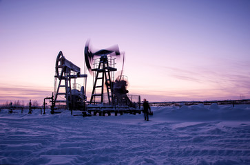 Oil worker in oilfield. Pump jack and engineer on a winter sunset sky background. Western Siberia.