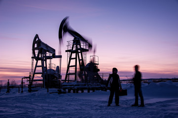 Oil workers in oilfield. Pump jack and engineer on a winter sunset sky background. Western Siberia.