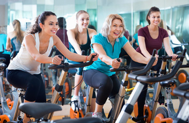 Elderly and young women working out hard in sport club
