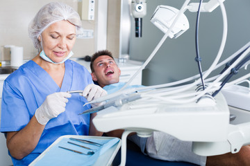 Dentist in dental clinic with patient behind