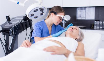 Cosmetician examining face skin of mature woman