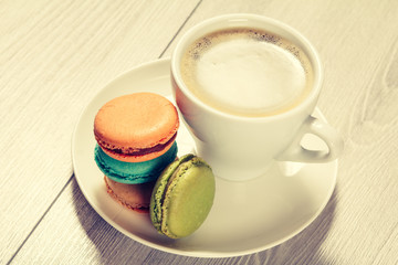 Cup of coffee and delicious macarons cakes of different color on white plate