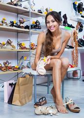Portrait of woman fitting picked summer footwear