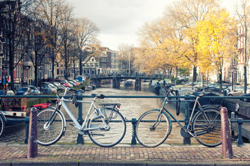 Bicycles lining a bridge over the canals of Amsterdam, Netherlands in vintage style.