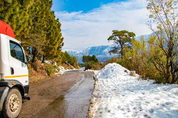 Scenic winter view from the asphalt road covered with snow and treess on the side of road on blue sky background and clouds