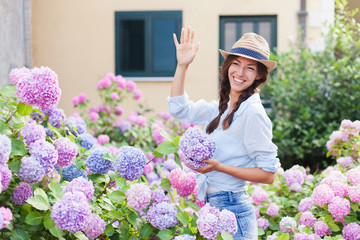 Fond de hotte en verre imprimé Hortensia Girl is in bushes of hydrangea flowers in blooming garden. Young woman greets neighbors or welcomes guests and visitors. Concept of countryside life style, gardening, hospitality.