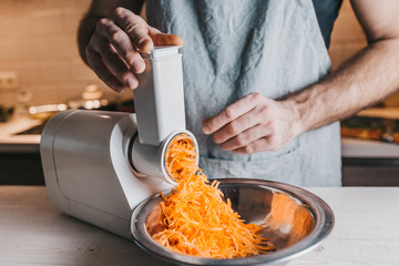Closeup of a rough male chef hands chopping carrots on an electric meat grinder