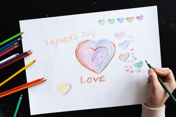 woman's hand draws pencils hearts on paper for valentine's day close up