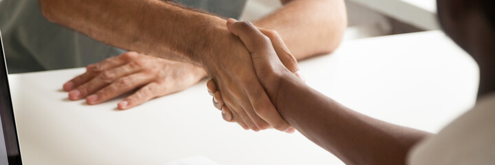 Close up hands of african and caucasian male shake hands express respect, greeting farewell symbol, boss meets client, successful negotiations concept, horizontal photo banner for website header