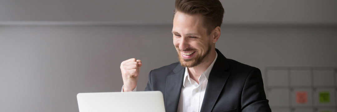 Horizontal photo happy businessman in suit sitting at desk look at laptop read receive great news online celebrate success win result concept, banner for website header design with copy space for text