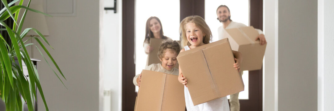 Horizontal photo happy family couple little children hold boxes belongings running into new house buying first home loan and mortgage concept. Banner for website header design with copy space for text