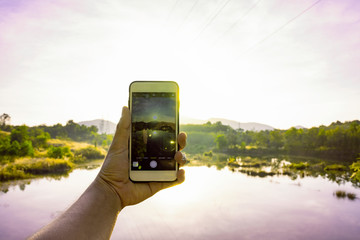 Hand hold mobile phone to take a photo of sunrise with beautiful yellow flare light in the morning, Landscape nature view of green mountain with sun light sky, Hand use mobile phone to capture photo