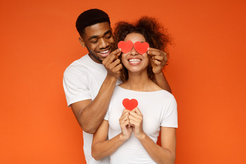Young couple holding red love hearts over eyes