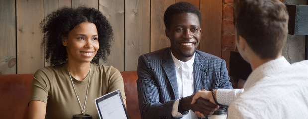 Horizontal photo happy black married couple meet with realtor agent broker at cafe, diverse people client consultant make deal greeting with handshake gesture concept, banner for website header design
