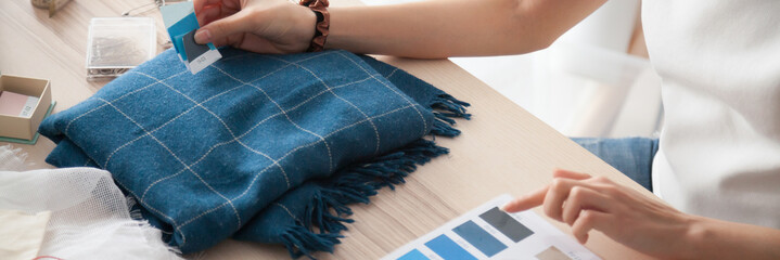 Close up busy fashion designer woman hands hold blue samples swatches make choose check color of textile fabric, dressmaker tailor occupation concept. Horizontal photo banner for website header design