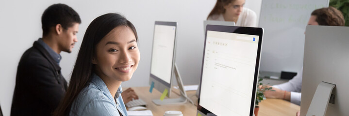 Smiling asian female worker looking at camera sitting at workplace working on pc with white mock up screen, diverse colleagues on background, banner for website header design with copy space for text