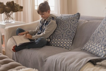 Boy reading a story book in living room
