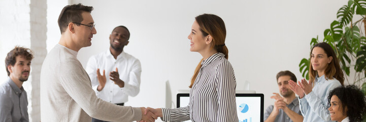 Boss handshaking with promoted female worker congratulating with success showing appreciation with good work result diverse colleagues clapping hands. Horizontal photo banner for website header design