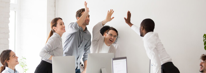 Fototapeta Happy diverse workmates giving high five celebrating corporate success feels excited in workplace, succeed common goal career growth concept, banner for website header design with copy space for text obraz