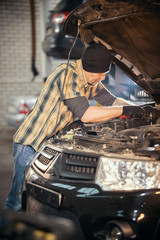 Car service. Brutal mechanic man standing by the car with open hood and inspects the car
