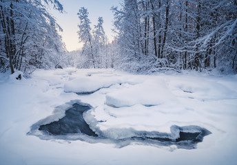 Scenic winter landscape with flowing river and morning light in Finland