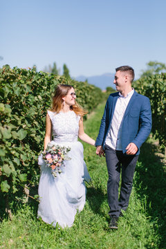 Happy young beautiful couple in blue clothes walking in the garden in sunny day. Couple in love smiling, hugging and kissing on the background of beautiful vineyard in Italy