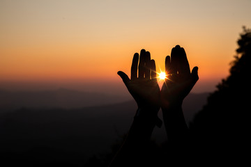 Lift hands to worship God with light sunset background. christian silhouette concept.