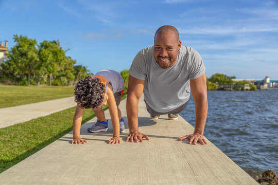A father smiles as he shows his young son how to do pushups on the seawall at the intercoastal. The young boy looks at dad teaching him to exercise as part of good health.