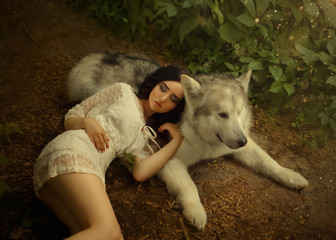 A petite girl with dark hair and soft cute face features is lying on gray-white forest wolf, doll in short white light dress resting on a big dog, a cute and attractive photo of fairy tale dream