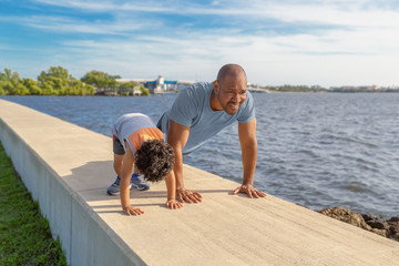 A father is showing his young son how to do pushups on the seawall at the intercostal. The young father is teaching his little by the importance of good health and exercise.