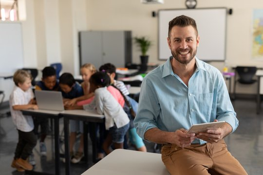 Teacher with digital tablet looking at camera