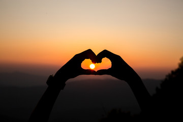 hands forming a heart with sunset background. love silhouette concept.