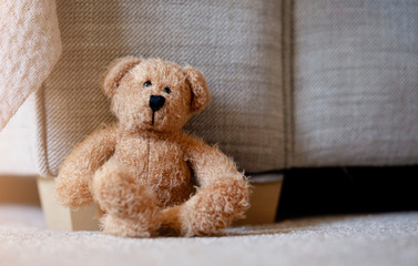 Teddy bear is sitting down on carpet in retro filter, Lonely teddy bear sitting alone in living room in sunny day, Lonely concept, International missing children's day.