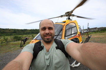 Selfie of a man with a beard on the background of a helicopter
