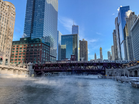 Elevated train crosses a freezing Chicago River as steam rises while temperatures plummet