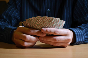 Man in darkness holding a set of playing cards, business strategic competition concept