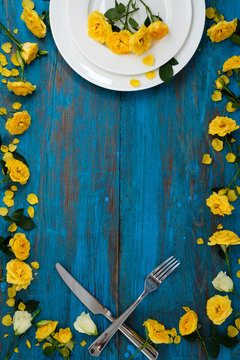 Easter table setting on blue wooden background with yellow spring flowers and eggs. Copy space.