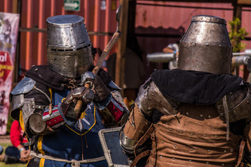 Medieval knights fighting with armor, swords and shields in festival