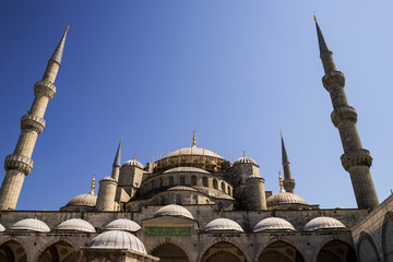 Bottom view of the Suleymaniye Mosque with two minarets against a blue sky.