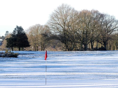 Snow covered golf course with red flag, Chorleywood Common, Hertfordshire, UK