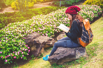 woman travel nature in the flower garden. relax sitting on rocks and reading books In the midst of nature at national park doi Inthanon.