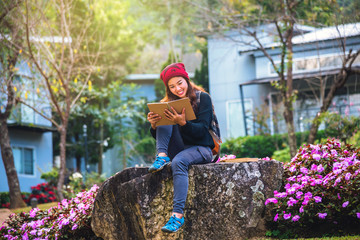woman travel nature in the flower garden. relax sitting on rocks and reading books In the midst of nature at doi Inthanon.