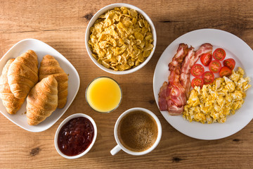 Breakfast with scrambled eggs, bacon, tomatoes,coffee,orange juice ,croissant and corn flakes on wooden table. Top view