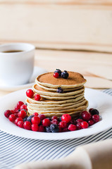 A stack of pancakes with blueberries and cranberries on a white plate.