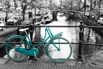 A picture of a lonely azure bike on the bridge over the channel in Amsterdam. The background is black and white.