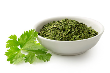 Dried chopped coriander leaves in white ceramic bowl next to fresh coriander leaves isolated on white.