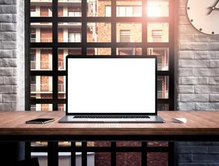 Laptop blank screen on table mockup loft style office