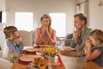 Family praying before having food on dining table