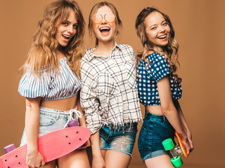 Three young stylish sexy smiling beautiful girls with colorful penny skateboards. Women in summer hipster checkered shirt clothes posing near golden wall in sunglasses. Positive models having fun